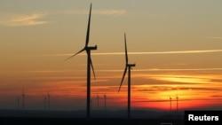 资料照片:法国坎布雷附近一个风力公园里的风力涡轮机掩映在夕阳之下。(2019年2月5日)