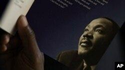 기념행사에서 마틴 루터 킹 2세 목사 사진이 프린트된 브로셔를 들고 있는 시민