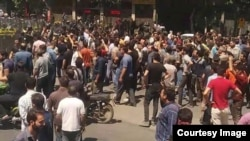 In this picture taken by a citizen journalist, Iranian security forces dressed in black confront anti-government protesters in Iran's third-largest city, Isfahan, during demonstrations that began July 31, 2018, and continued Aug. 1, 2018.