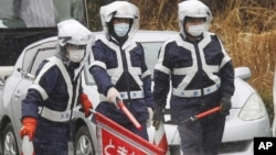 Police officers wearing face masks inspect vehicles at the entrance of a 20km no-entry zone, on the outskirts of Hirono town, Fukushima prefecture, Japan, March 2012. (file photo)