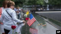 FILE - Visitors touch the names of the victims of the Sept. 11, 2001, terror attacks at the South Pool of the National September 11 Memorial, Sept. 11, 2015, in New York.