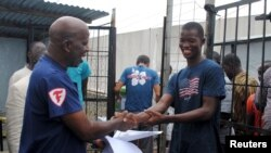 FILE - Cassius Kollie (R), 24, one of four people discharged from an Ebola treatment unit, receives a certificate for being cured of the disease in Paynesville, Liberia, July 20, 2015.