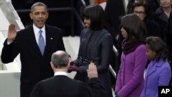 Presiden Barack Obama (kiri), disaksikan ratusan keluarganya dan ratusan ribu warga AS, mengambil sumpah jabatan. di depan gedung Capitol di Washington DC hari Senin (21/1).