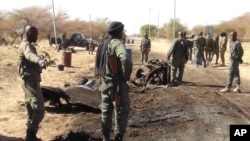 Malian soldiers stand around the debris left after a jihadist suicide bomber blew himself up. (March 2013)