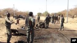 Sur cette photo prise le 21 mars, 2013, des soldats maliens se tiennent autour des débris laissés après un attentat-suicide à un barrage de l'armée malienne près de l'aéroport de Tombouctou, au Mali.