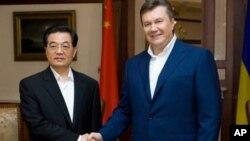 ປະທານາທິບໍດີ Viktor Yanukovich , ເບື້ອງຂວາ, ຈັບມືກັບ ປະທານປະເທດຈີນ ທ່ານຫູຈິນເຖົາ ໃນການພົບປະກັນທີ່ເມືອງ Foros, ໃກ້ກັບເມືອງ Yalta, ວັນທີ 18 ມິຖຸນາ, 2011.