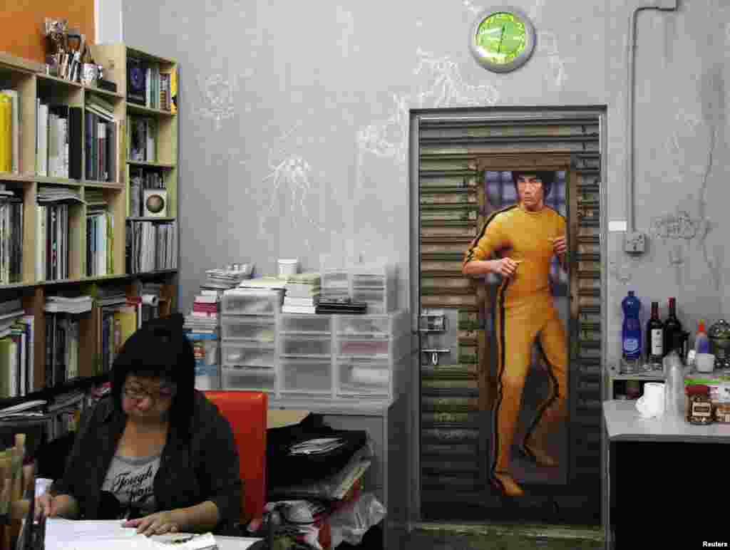 A woman works inside a Hong Kong gallery exhibiting paintings of the late kung fu legend Bruce Lee by local artists. Fans are marking his death 40 years ago this weekend with art gallery shows, exhibitions and even street graffiti, though some people are urging Hong Kong's government to do more to honor the former British colony's biggest star.