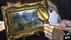 An art shopper looks closely at a 5.5 inch by 6.6 inch painting by French Impressionist master Pierre-Auguste Renoir in Alexandria, Virginia, September 25, 2012.