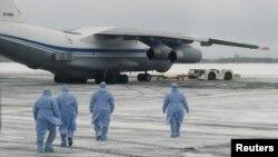 身穿防護服的俄羅斯醫務人員走向從中國武漢撤回俄羅斯與東歐國家僑民的軍機。(2020年2月5日)