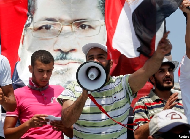 Supporters of ousted President Mohamed Mursi shout slogans as they attend weekly Friday prayers at Rabaa Adawiya square, where they are camping, in Cairo July 12, 2013