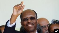 ອະດີດປະທານາທິບໍດີ Jean-Bertrand Aristide ໂບກມື ຫລັງຈາກກອງປະຊຸມຖະແຫລງຫລັງຈາກໄປຮອດສະໜາມບິນລະ ຫວ່າງຊາດທີ່ນະຄອນຫລວງ Port-au- Prince ວັນທີ 18 ມີນາ 2011.