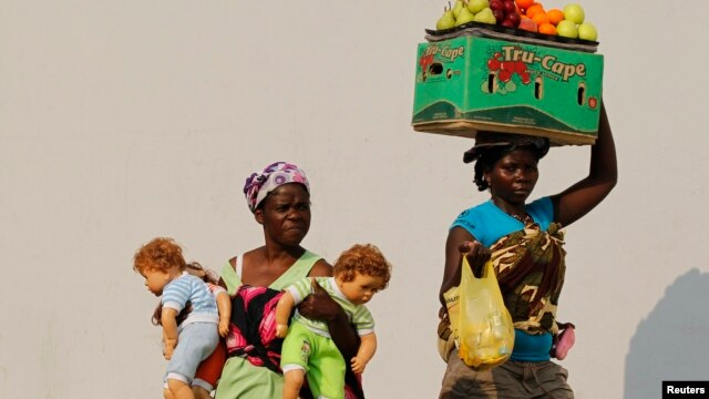 Hawkers walk past each other in the capital  Luanda, Aug. 28, 2012.