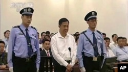 In this image taken from video, disgraced politician Bo Xilai, center, stands in the courtroom, flanked by police guards at Jinan Intermediate People's Court in eastern China's Shandong province, Aug. 22, 2013.