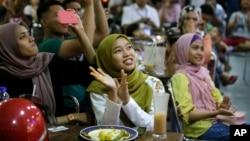 Warga Malaysia di sebuah restoran bersorak-sorai menonton televisi saat Mahathir Mohamad dilantik sebagai PM Malaysia ke-7 di Kuala Lumpur, Kamis (10/5).