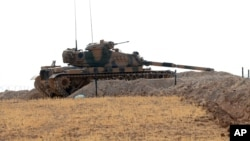 FILE - A Turkish tank is stationed near the Syrian border, in Karkamis, Turkey, Aug. 29, 2016.