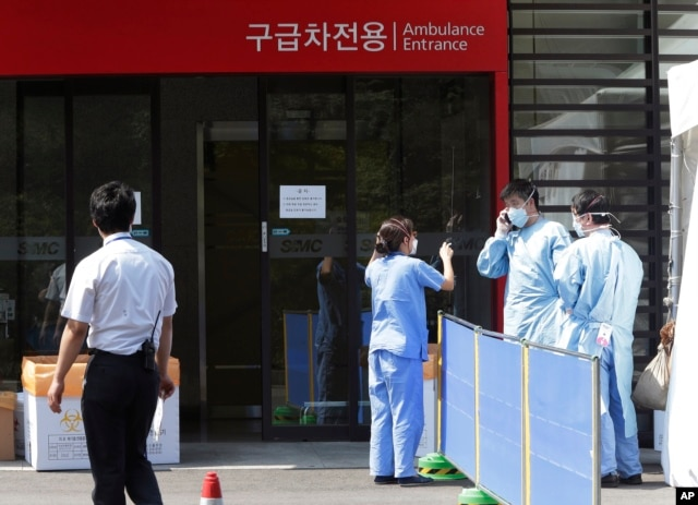FILE - Hospital workers wear masks as a precaution against the Middle East Respiratory Syndrome (MERS) virus as they work in front of an emergency room of Samsung Medical Center in Seoul, South Korea, June 7, 2015.