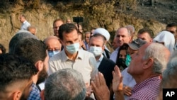 In this photo released Tuesday, Oct. 13, 2020 on the official Facebook page of the Syrian Presidency, Syrian President Bashar Assad, center, wearing a mask to help prevent the spread of the coronavirus, speaks with people during his visit to the coastal province of Latakia, Syria