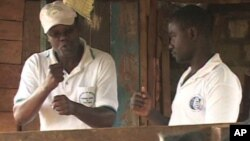 FILE: Joseph Shiroko, founder of Brian Resource Center, communicates with a student in sign language