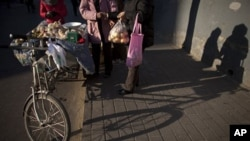 A woman, right, pays money to a street vendor, center, for a bag of apple she bought near the vendor's tricycle cart in Beijing, China, 11 Dec 2010