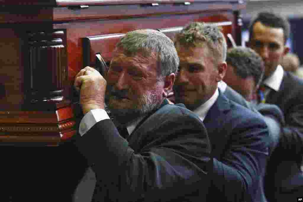 Gregory Hughes, left, father of Phillip Hughes, helps to carry Phillip's coffin during his funeral in Macksville, Australia. Cricketer Phillip Hughes, 25, died on Nov. 25 after being hit near the ear by a ball during a match between South Australia and his former state side New South Wales at the Sydney Cricket Ground.