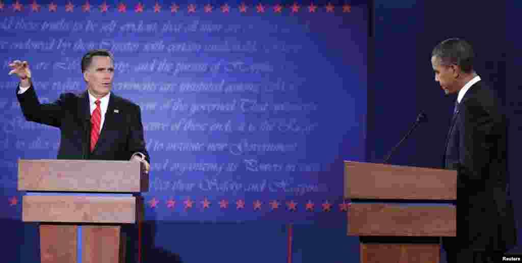 El presidente Barack Obama escucha al candidato republicano Mitt Romney. Algunos analistas indicaron que el mandatario estuvo a la defensiva en la discusión.