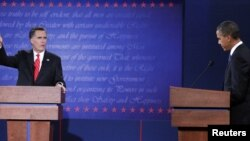 President Barack Obama (kiri) menyimak saat capres dari partai Republik, Mitt Romney berbicara dana debat pertama calon presiden AS di Denver (3/10).