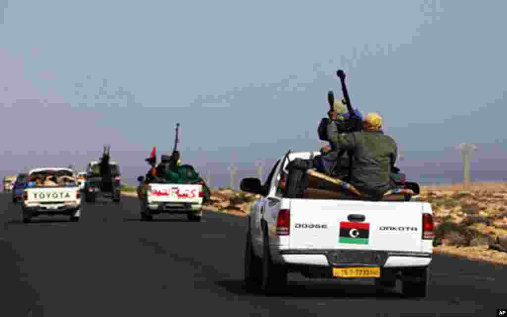 Rebels travel in a convoy on their way to Sirte city near Bin Jawad March 28, 2011. A steady stream of rebels in 4x4 pick-ups mounted with machineguns drove in the direction of Libyan leader Muammar Gaddafi's hometown of Sirte on Monday, seeking to extend