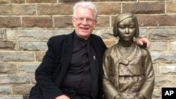 Uniting Church minister Bill Crews poses for a photo with a statue erected as a memorial to sex slaves of Japan's World War II army in Sydney, Australia, Aug 6. 2016. A Japanese-Australian community leader said Thursday he had filed a complaint of racial discrimination against the Sydney church that he alleged intimidated Japanese nationals by erecting a memorial to sex slaves of Japan's World War II army.