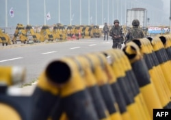 FILE - South Korean soldiers walk by barricades on the road leading to North Korea's Kaesong joint industrial complex at a military checkpoint in the border city of Paju, Aug. 21, 2015.