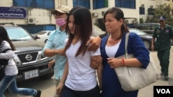 Kum Chandaraty, left, walks with her lawyer, Try Chhoun, after being questioned by the Ministry of Interior's anti-terrorism department on Friday. (Photo: Neou Vannarin/VOA Khmer)