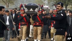 'Yan sanda dauke da gawar Gwaman Punjab na Kasar Pakistan da aka hallaka. da aka hallaka Pakistani police guards carry the coffin of late Punjab governor Salman Taseer during the funeral procession in Lahore on January 5, 2011. Thousands of Pakistanis br