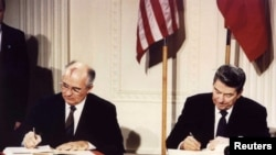 Президент США Рональд Рейган и президент СССР Михаил Горбачев подписывают Договор о РСМД. Белый дом. 8 декабря 1987.