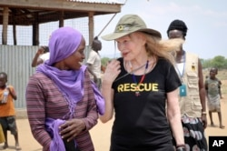 FILE - Human rights activist Mia Farrow talks with staff from the International Rescue Committee while visiting an internally displaced persons camp in Juba, South Sudan. As envoy for the International Rescue Committee, she is helping the aid group promote a global initiative to change the way humanitarian organizations approach malnutrition.