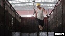 一名工人在河北唐山一家仓库里往卡车上装钢筋 (2015年路透社资料照)