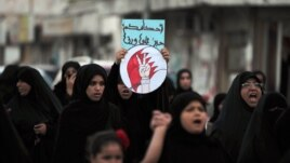 "FILE - A Bahraini anti-government protester carries a sign with the words, ""Oh, jailer, your sentences will not frighten us,"" during a march in the western village of Malkiya, Bahrain, October 3, 2013."