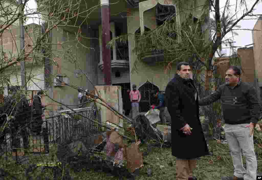 Civilians inspect their damaged house after a car bombing in the Hurriyah neighborhood of northern Baghdad, Feb. 3, 2014.