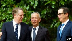 Wakil Perdana Menteri China Liu He didampingi oleh Perwakilan Dagang AS Robert Lighthizer (kiri) dan Menteri Keuangan Steven Mnuchin, menyambut media sebelum pertemuan perdagangan tingkat menteri di Washington, Kamis, 10 Oktober 2019. (Foto AP / Jose Luis Magana)