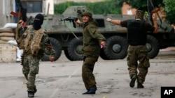 Para pemberontak pro-Rusia menari sambil menembakkan senjata ke udara di Donetsk, Ukraina timur (27/6). (AP/Dmitry Lovetsky)