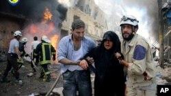 叙利亚民防人员正在帮助一位在战机袭击阿勒颇一条街道后受伤妇女,2016年6月8日。
