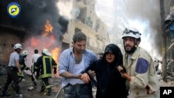 FILE - This photo taken June 8, 2016, and provided by the Syrian Civil Defense Directorate in Aleppo province, shows Syrian civil defense workers helping an injured woman after warplanes attacked a street, in Aleppo, Syria.
