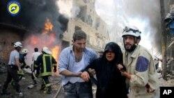 Lực lượng dân sự Syria giúp đỡ một người phụ nữ bị thương sau khi máy bay chiến đấu tấn công một con phố ở Aleppo, ngày 8/6/2016.
