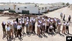 Para anggota Mujahedeen-e-Khalq organization meneriakkan slogan dan memegang spanduk saat pemerintah Iraq menggelar kunjungan luar biasa bersama diplomat asing di kamp Liberty, dekat Baghdad (Foto: dok). Para pejabat Irak mengatakan sejumlah penyerang menembakkan roket ke kamp Liberty ini, menewaskan sedikitnya lima orang dan melukai 40 lainnya, Sabtu (9/2).