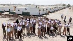 伊朗人民圣战者组织成员在伊拉克政府组织国际外交官参观首都城外难民营时举起标语并呼喊口号。(2012年9月11日)