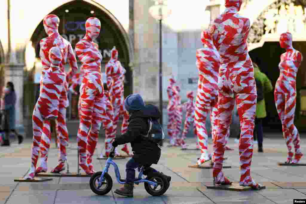 "A little boy looks at an art installation with 111 mannequins on Marienplatz calling for more ""mindfulness and appreciation"" in times of the pandemic in Munich, Germany."