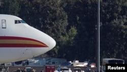 Сотрудники CDC в спецзащитных костюмах ожидают высадки пассажиров, эвакуированных из Уханя, на аэродроме базы ВВС в Риверсайде, Калифорния, 29 января 2020 года
