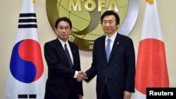 윤병세 한국 외교부 장관(오른쪽)과 기시다 후미오 일본 외무상이 28일 한국 외교부에서 만나 악수하고 있다.