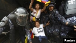 Nepalese police personnel detain Tibetan activists during their protest near the Chinese Embassy Consular office in Kathmandu on March 10, 2014.