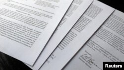 FILE - US Attorney General William Barr's signature is seen on a four-page letter to U.S. congressional leaders on the conclusions of Special Counsel Robert Mueller's report on Russian 2016 election meddling after the letter was released by the House Judi