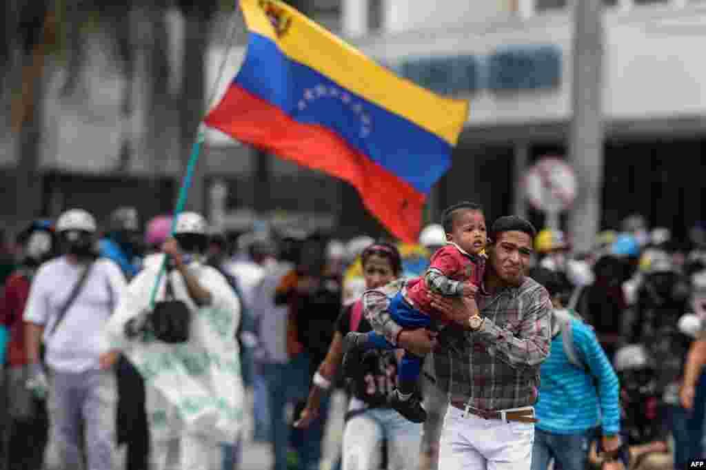 មនុស្សម្នារត់គេចក្នុងពេលប៉ះទង្គិចមួយរវាងបាតុករ និងប៉ូលិសនៅក្នុងបាតុកម្មមួយប្រឆាំងនឹងរដ្ឋាភិបាលរបស់លោកប្រធានាធិបតី Nicolas Maduro នៅក្នុងក្រុង Caracas វ៉េណេស៊ុយអេឡា។