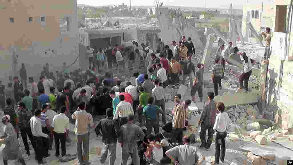 شامی طیاروں کی بمباری کے بعد لوگ ایک عمارت کے ملبے میں دب جانے والوں کی مدد کے لیے جمع ہیں۔